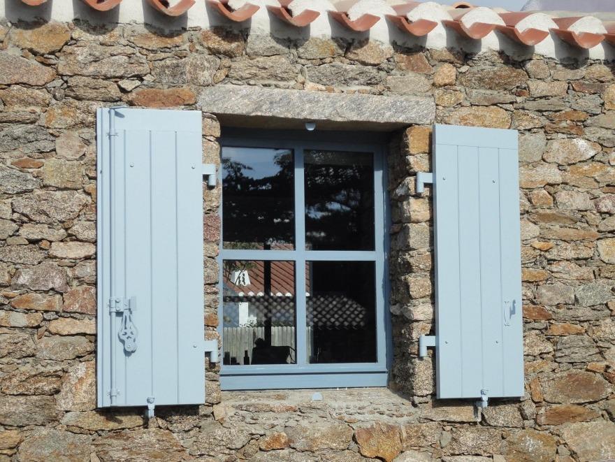Fenêtre en acier sur une maison en pierre