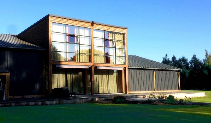 Maison d'architecte avec une grande baie vitrée en acier