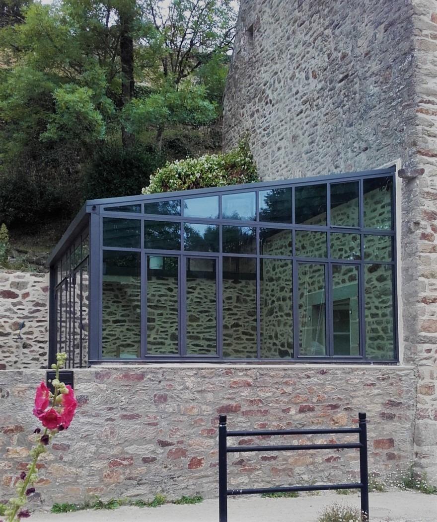 véranda en acier maison en pierre