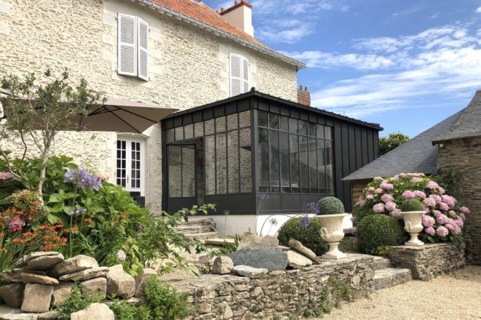 Véranda en acier sur une maison en pierre
